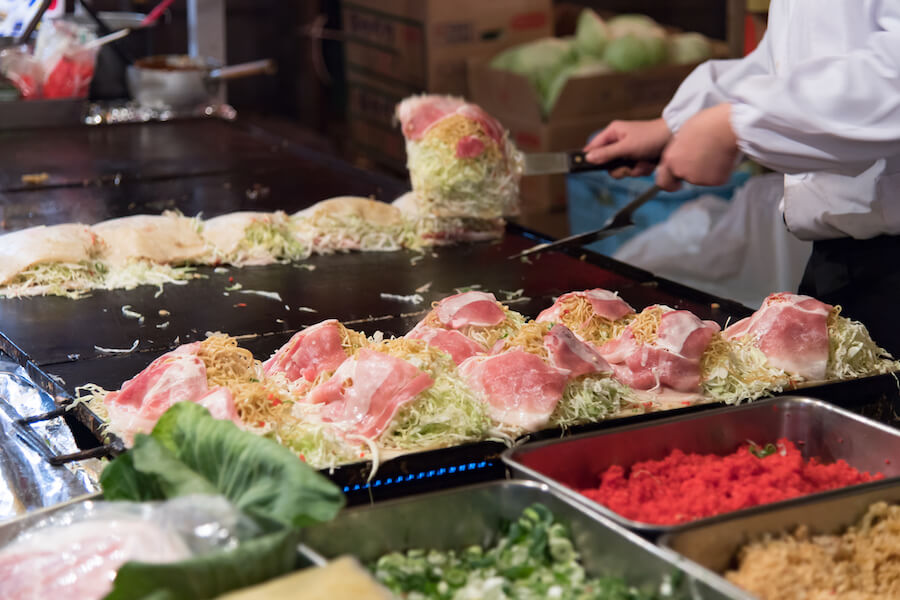 Okonomiyaki cooking by the chef - 10 Food you need to try in Japan
