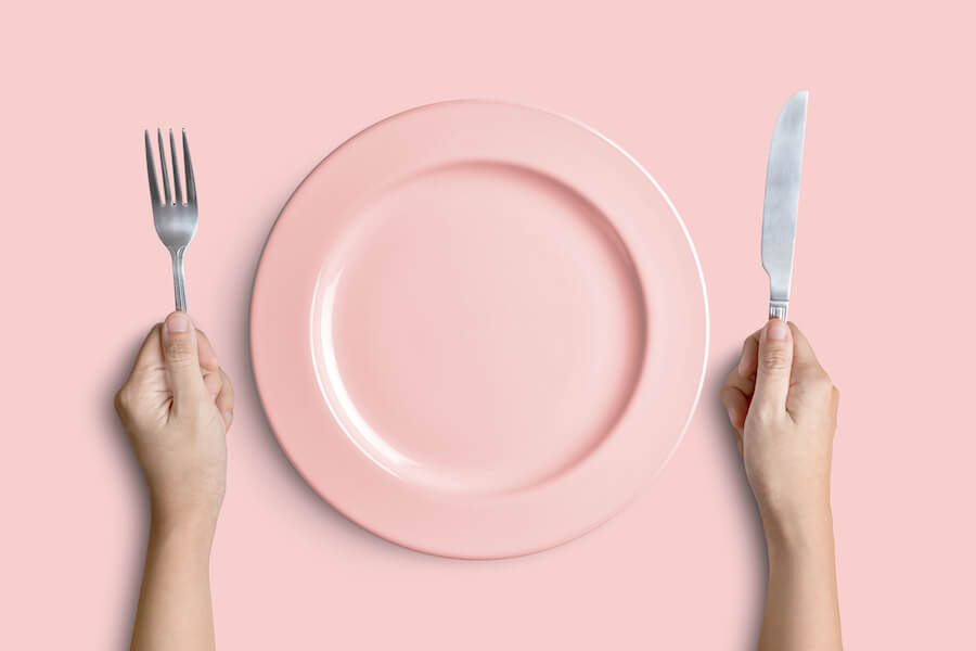 Pink plate with silver fork and knife on pink background - how to get into ketosis