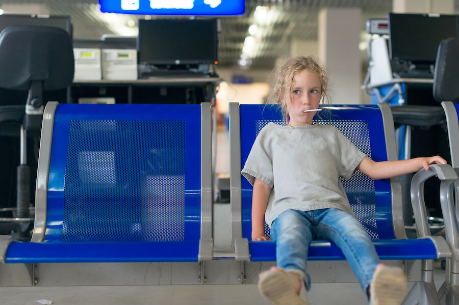 Little girl waiting for flight at airport with a lollipop - Airline Travel Hacks