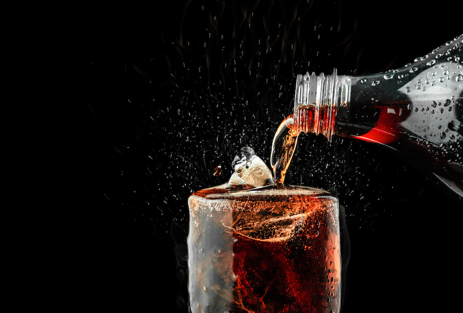 Pour soft drink in glass with ice splash on dark background - Airline Travel Hacks