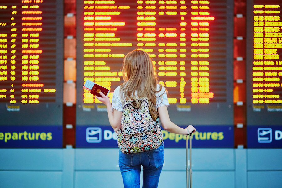 Tourist girl with backpack in international airport - Airline Travel Hacks
