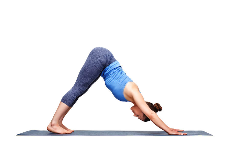 Beautiful sporty fit yogi girl practice downward facing dog - yoga poses for flexibility