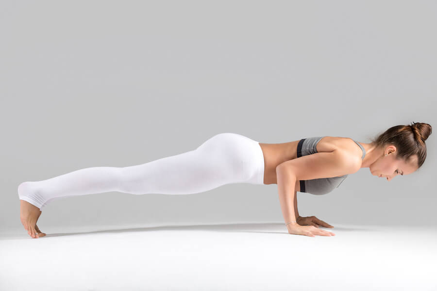 Young woman in chaturanga dandasana pose, grey studio background - yoga workout for weight loss