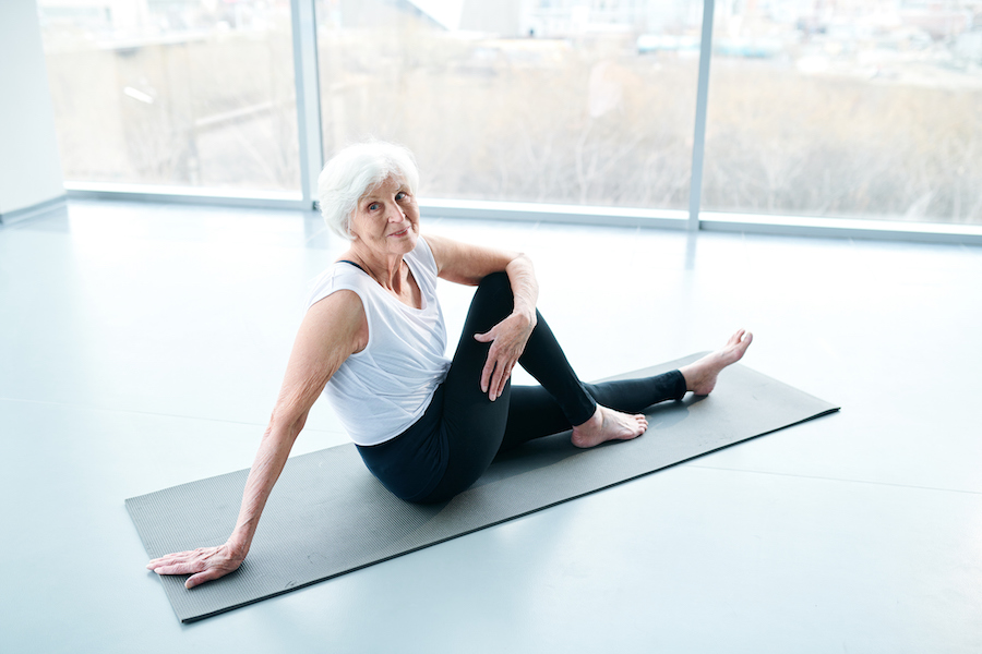 Senior woman on yoga mat - Yoga for older women