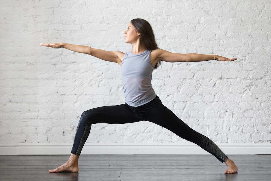 Young attractive woman in Warrior two pose - Yoga for Older Women