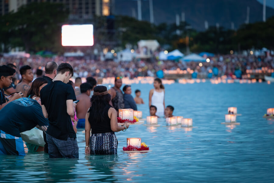 Young couple placing prayer lantern in water Honolulu, Hawaii - Best places to visit each month of the year