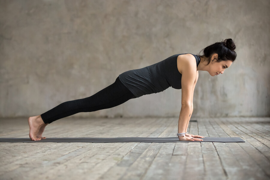Young woman in Plank pose - yoga workout for weight loss