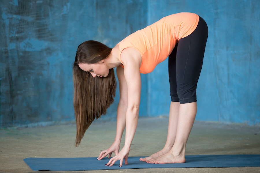 Sporty attractive young woman Doing Ardha Uttanasana pose - Yoga Workout For Flexibility