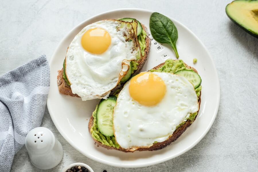 Breakfast toast with fried egg, avocado and cucumber with whole grain bread on white plate - foods that burn belly fat