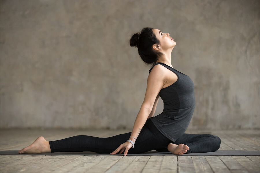 Young woman doing Single Pigeon exercise - Yoga Workout For Flexibility