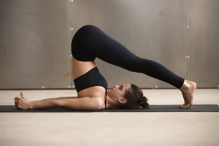 Young attractive woman stretching in Halasana pose - Yoga Workout For Flexibility