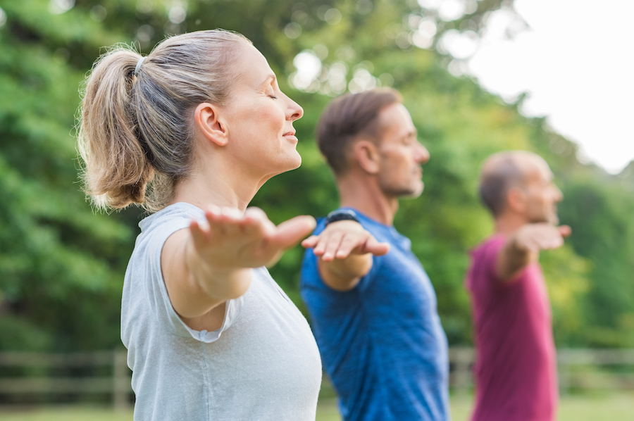 yoga group practicing outdoor - health benefits of yoga that makes you practice every day