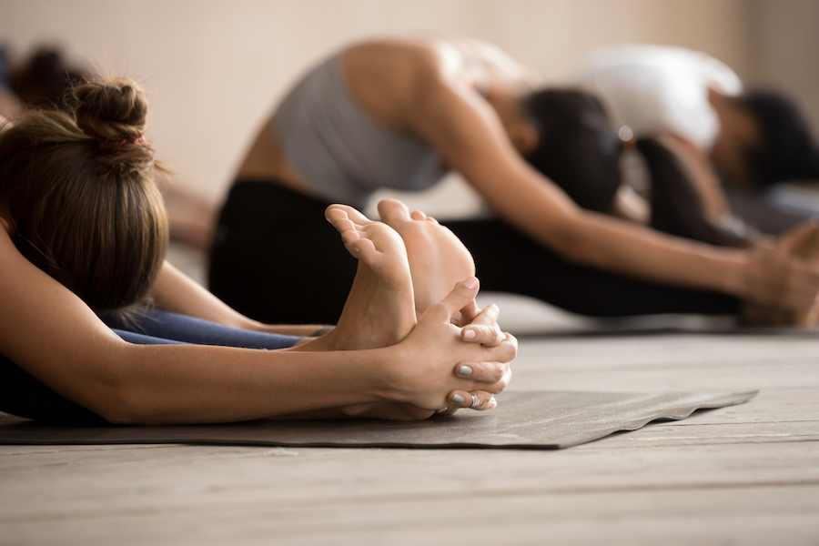 yoga group touching toes - health benefits of yoga that makes you practice every day