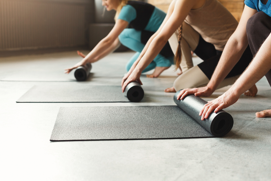 rolling out yoga mat and preparing for training - best yoga mats