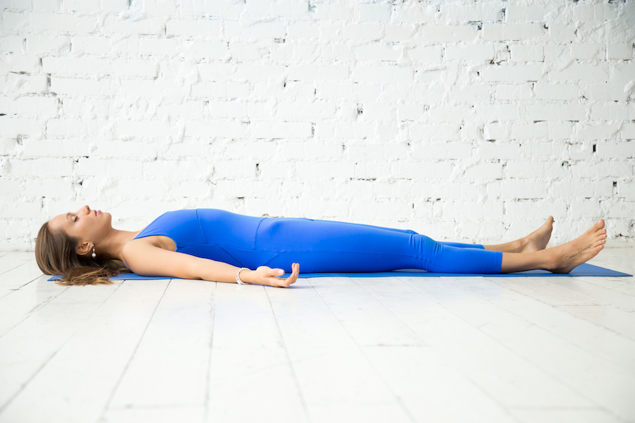 Young attractive woman in corpse pose - yoga sequence for anxiety and stress