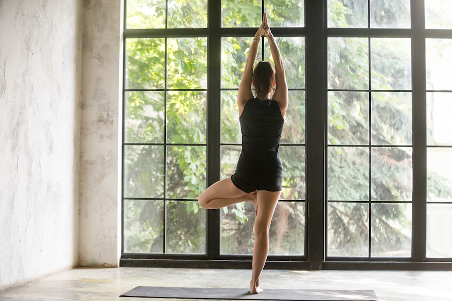 Young sporty woman in Vrksasana pose, window background - yoga sequence for anxiety and stress