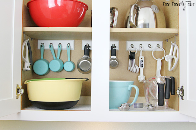 Stick Command Hooks in your kitchen cabinet - brilliant ways to organize kitchen cabinets
